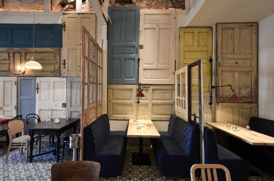 Restaurant interior made out of salvaged doors windows for Recycled interior doors